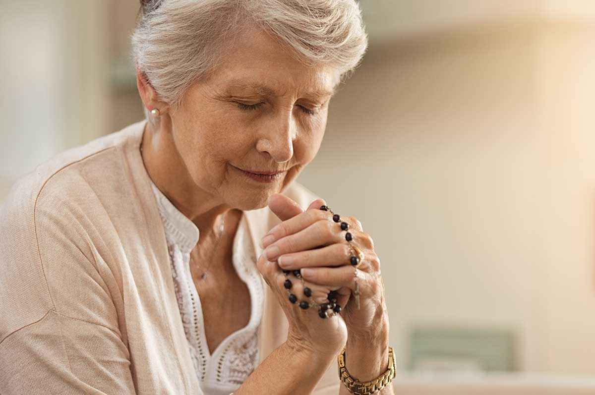 senior woman praying and holding rosary beads