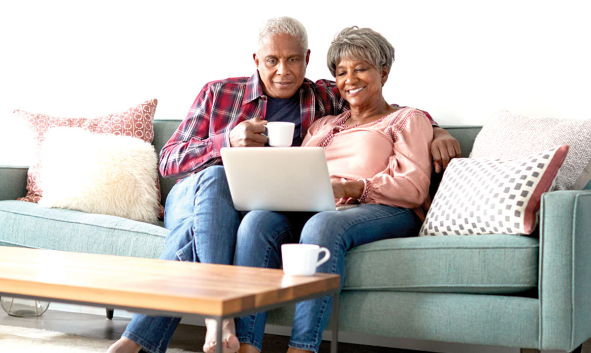 Senior Couple Sitting On Sofa At Home Using Laptop To Watch Senior Choice at Home Online Event