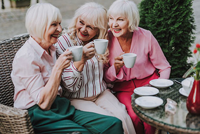 Senior Ladies Talking, Smiling and Drinking Tea