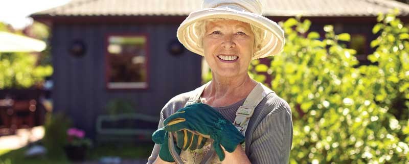 Woman smiling while she is working outside in her yard