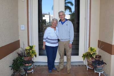 Elderly couple standing in front of their house smiling
