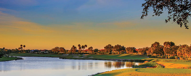 Photo of golf course and lake at sunset